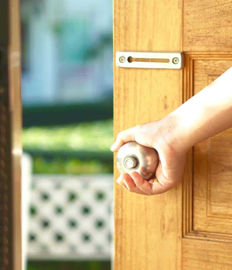 Hand holding the handle of a security door