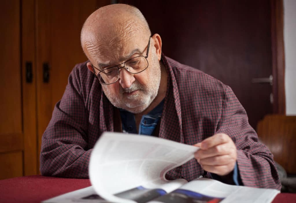 man reading statements from a magazine