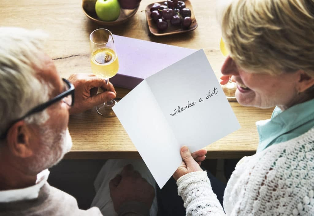 retiree couple reading a thank you card
